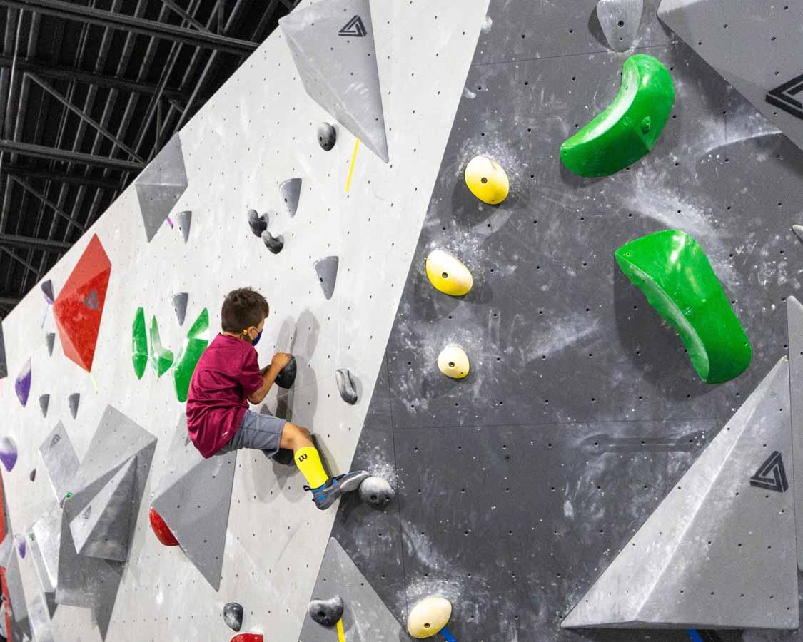 Child bouldering at La Crux Laval climbing gym