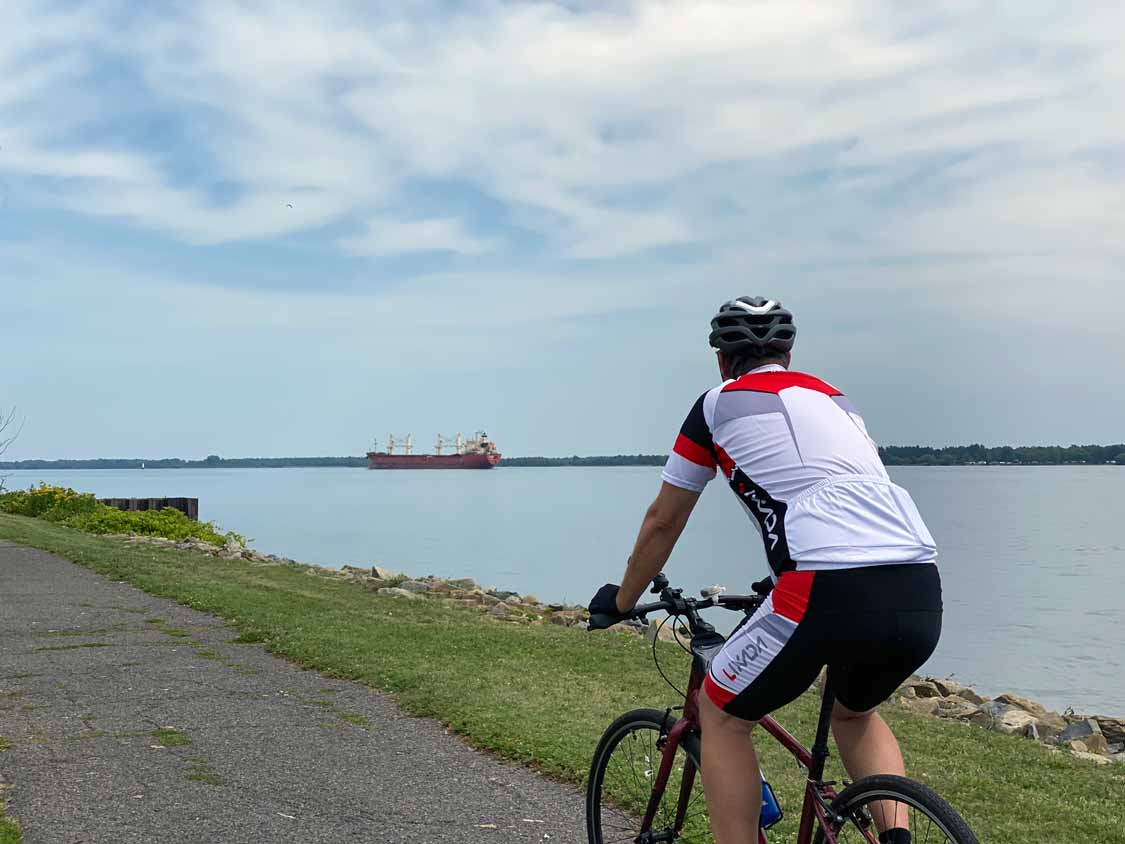 Cyclist watches a cargo ship in the St. Lawrence River