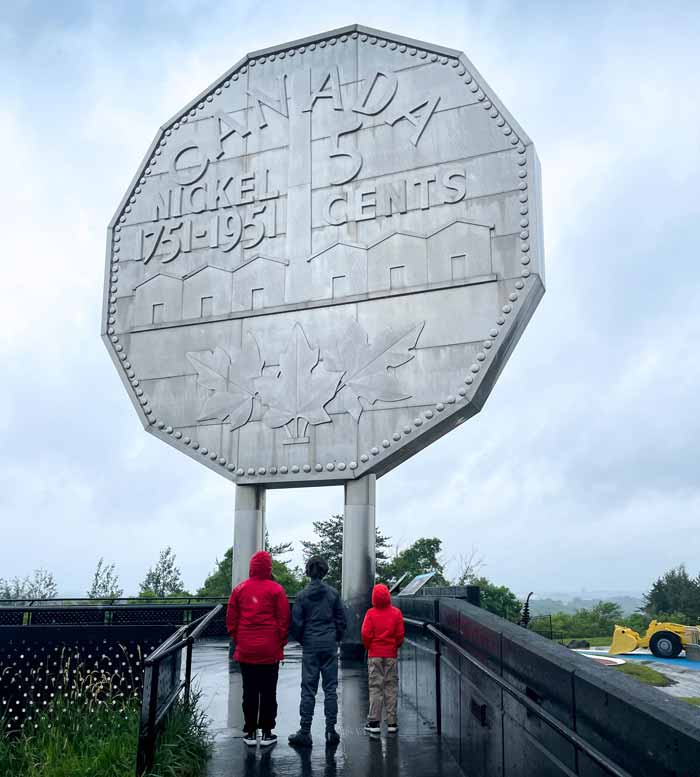 A family gazes up at the Big Nickel in Sudbury at Dynamic Earth