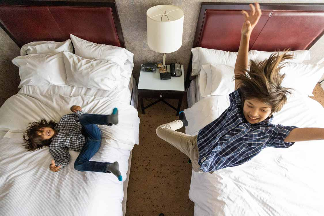 Kids jumping on a bed at the Westin Harbour Castle in Toronto
