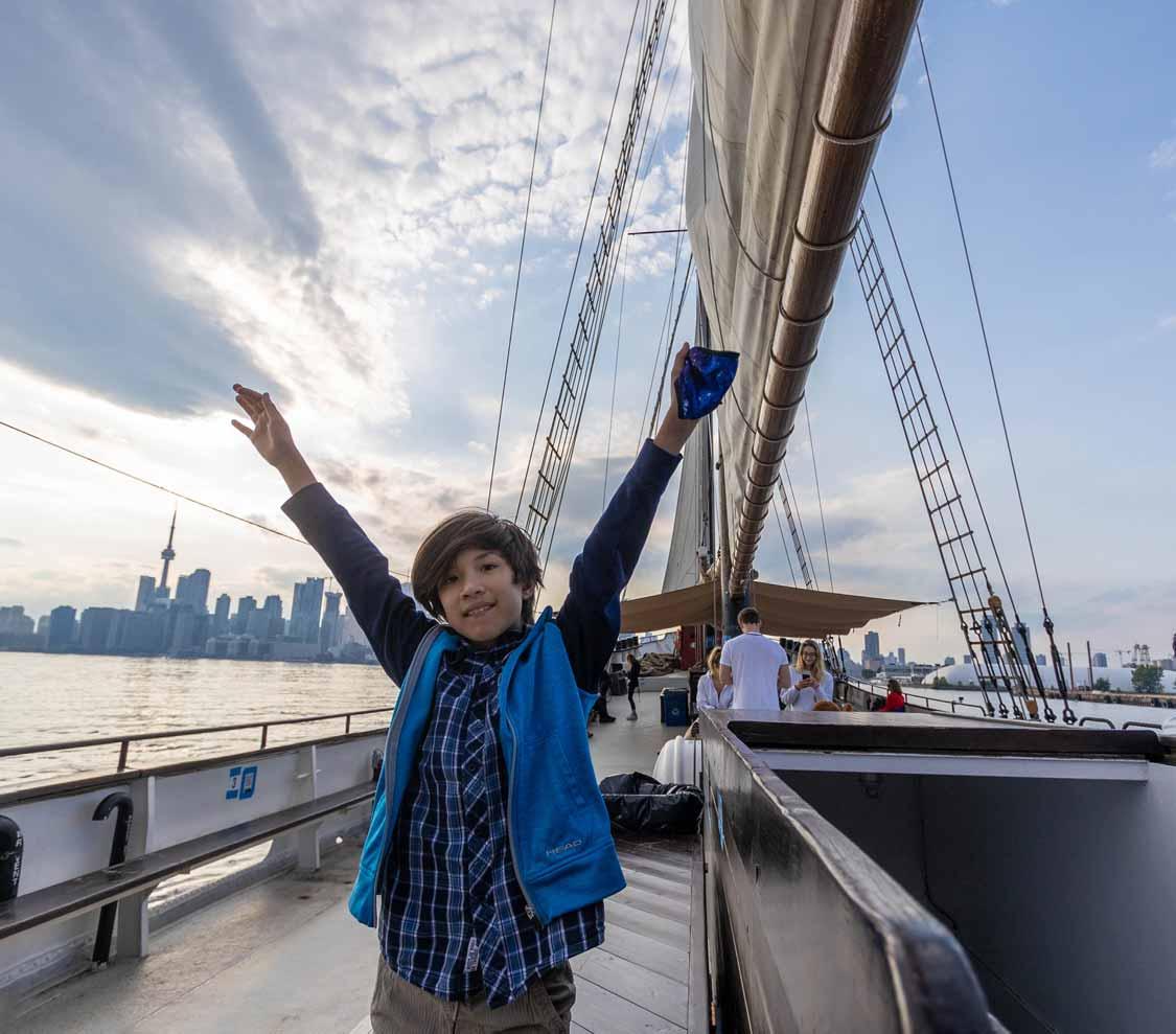 A boy raises his arms on the Tall Ship Kajama in Toronto for families