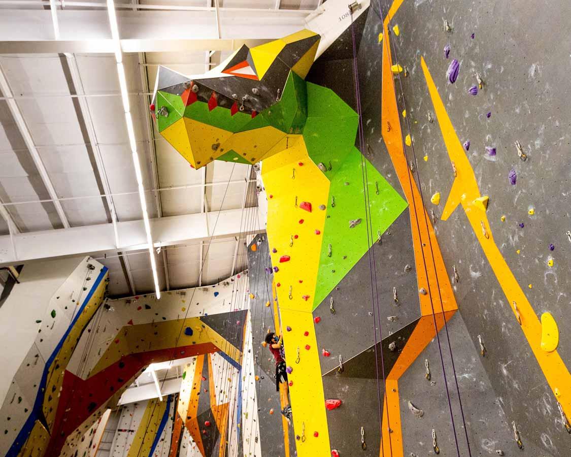 A boy climbs the Dragon climbing wall at Hub Climbing Mississauga