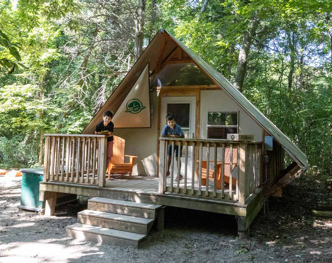 Boys standing on the deck of a glamping oTENTik at Point Pelee National Par